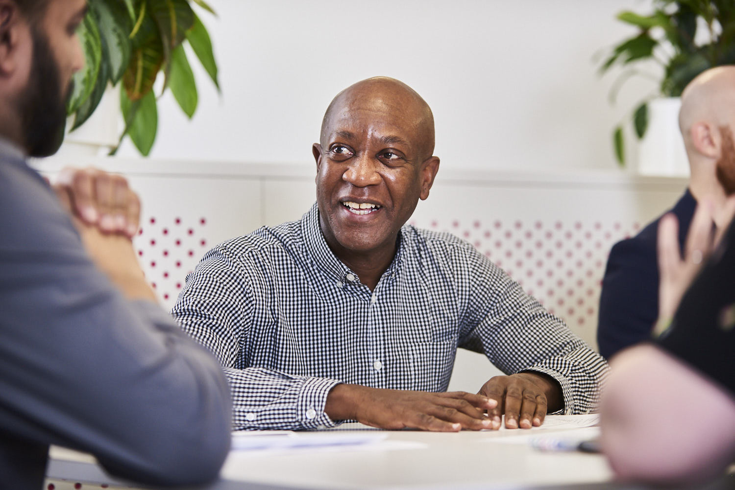 Man smiling in a bright meeting room in the middle of a team meeting
